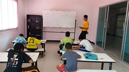 Tong Tong i fuld gang med at undervise immigrantbørnene.